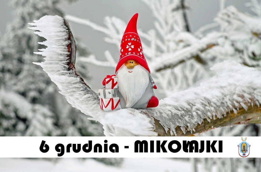 Na plakacie widnieją zapisy: 8 grudnia Mikołajki. W tle widać zamarznięte gałęzie pokryte lodem i  śniegiem oraz mikołajka siedzącego na gałęzi w czerwonej czapce i prezentami.