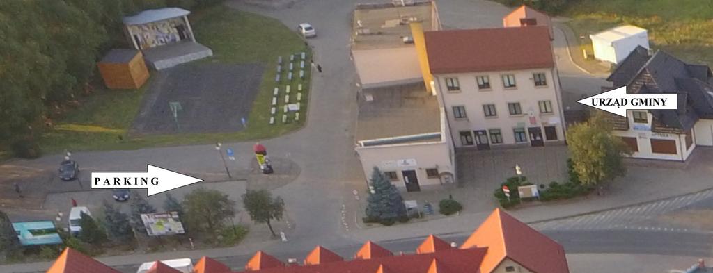 Zdjęcie budynku urzędu gminy - widok z góry, od strony ulicy Trzebnickiej. Zaznaczono strzałką po lewej stronie parking, a po prawej stronie urząd.