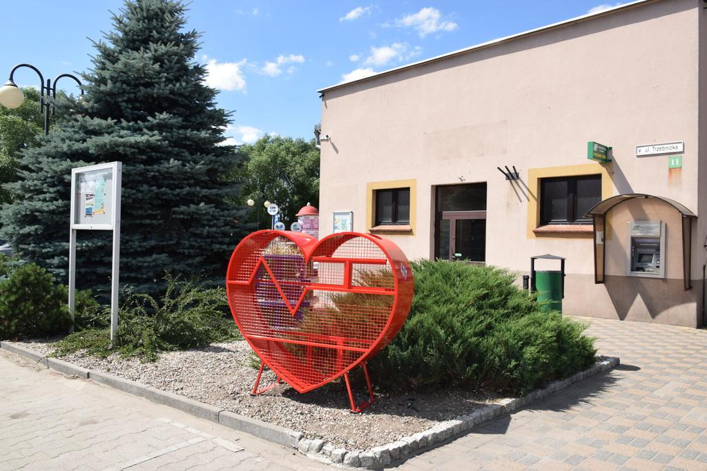 Na zdjęciu widać czerwone, stalowe serce, które znajduje się przez parkingiem przed Urzędem Gminy Zawonia, przed bankomatem.