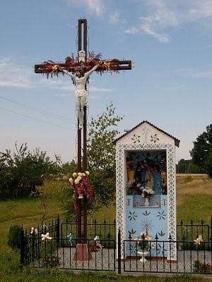 Zdjęcie przedstawia przydrożna kapliczkę wraz z krzyżem w miejscowości Pęciszów