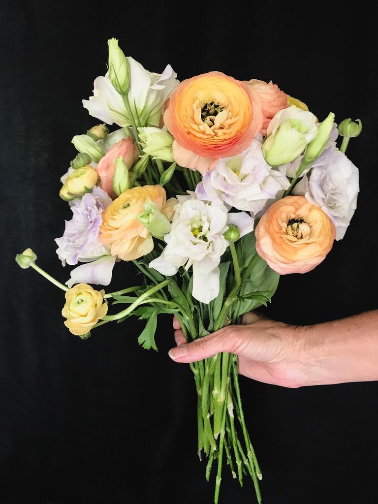 Na zdjęciu na czarnym tle, widać bukiet kolorowych kwiatów, trzymanych w dłoni