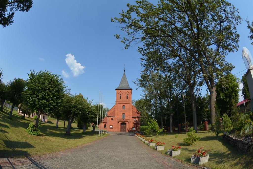 Zdjęcie przedstawia kościół w Czeszowie i kapliczkę