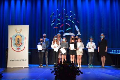 Na zdjęciu widać nagrodzonych uczniów z ich rodzicem oraz z Panią Wójt, która wcześniej wręczyła im dyplomy i statuetki. Obok uczniów stoi baner z herbem gminnym. Przed sceną widoczny jest bukiet kwiatów.