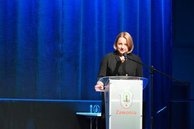 Na zdjęciu widać, jak na scenie, przy mównicy przemawia Wójt Gminy Zawonia