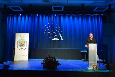 Na zdjęciu widać, jak na scenie, przy mównicy przemawia Wójt Gminy Zawonia. W lewej stronie znajduje się baner z herbem gminy.