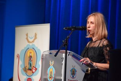 Na zdjęciu widać, jak na scenie, przy mównicy przemawia Dyrektorka GOK. W lewej stronie znajduje się baner z herbem gminy.