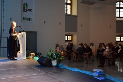 Na zdjęciu widać osoby, które przybyły na Galę Edukacji Narodowej. Na scenie przemawia Dyrektorka GOK