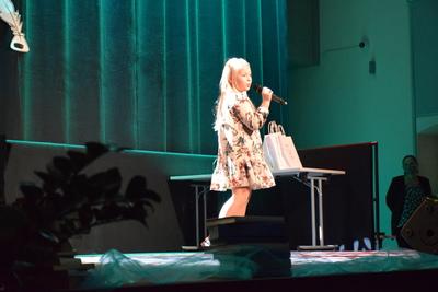 Na zdjęciu widać, jak na scenie śpiewa dziewczynka, która jest uczennicą Szkoły Podstawowej w Czeszowie