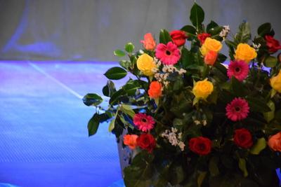 Na zdjęciu widać w tle scenę oraz bukiet kwiatów złożony z kolorowych gerber-ów, róż i zielonych ozdobnych liści