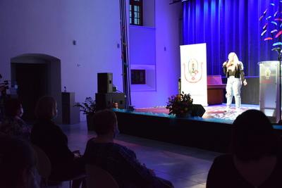 Na zdjęciu widać, jak na scenie śpiewa dziewczyna, która jest uczennicą Zespołu Szkół w Zawoni