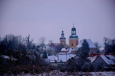 Na zdjęciu widać dwie wieże: jedna kościoła, drugą Gminnego Ośrodka Kultury, wszystko dokoła jest pokryte śniegiem