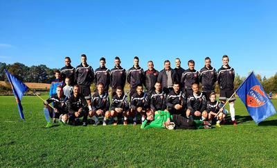 Na zdjęciu widać cały skład drużyny piłkarskiej SKS Victoria Zawonia wraz z sympatykami, trenerami oraz widoczne są dwie flagi z logo Victorii