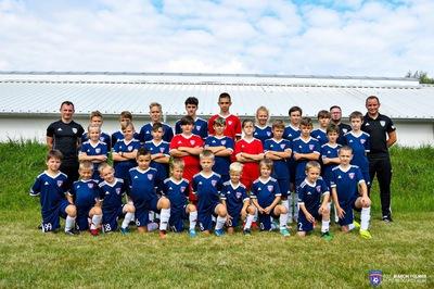 Na zdjęciu widać dzieci wraz z dwoma trenerami, trenujące w Akademii Piłkarskiej FreeKids