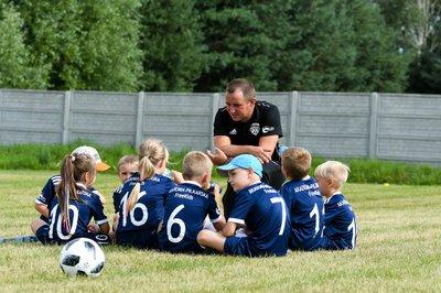 Na zdjęciu widać trenera wraz z dziećmi, który tłumaczy im zasady gry w pikę nożną. Dzieci należą do Akademii Piłkarskiej FreeKids