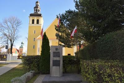 Na zdjęciu widać pomnik Wojska Polskiego – 2 Dywizji Artylerii oraz 100-lecia Odzyskania Niepodległości, a w tle kościół poewangelicki, w którym obecnie znajduje się Gminny Ośrodek Kultury