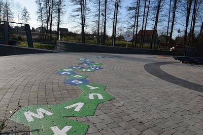 Na zdjęciu widoczny jest element Zielonej Strefy Aktywności, która znajduje się w Zawoni przy ulicy Zielonej. Są to gry i zabawy uliczne - białe literki na zielonym tle