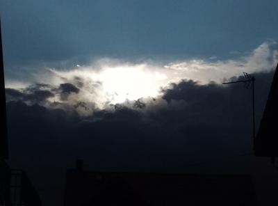 Na zdjęciu widać zachmurzone niebo i przebijające się słońce