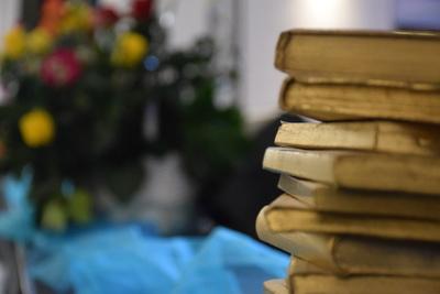 Na zdjęciu widać stos ułożonych złotych okładek książek oraz kwiaty w tle