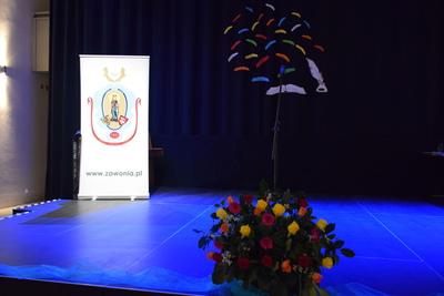 Na zdjęciu widać scenę Sali Widowisk w GOK, przed sceną kwiaty w tle herb Gminy Zawonia