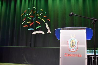 Na zdjęciu widać scenę Sali Widowisk w GOK, w tle herb Gminy Zawonia, z prawej strony znajduje się mównica