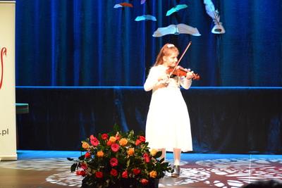Na zdjęciu na scenę gra na skrzypcach uczennica gminnej szkoły