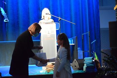 Na zdjęciu widać jak Pani Wójt wręcza dziewczynce grającej na skrzypcach gadżet za pomyślny występ podczas Gali Edukacji Narodowej